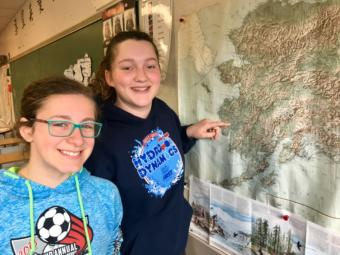 Mackenzie Olver (left) and Sandra Bouvier point out Akiuk on a map of Alaska at Dzantik'i Heeni Middle School on April 17, 2019. (Photo by Zoe Grueskin/KTOO)