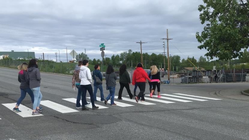 Anchorage residents walk across Fourth Avenue during a tour led by Partners Reentry Center on May 24, 2019.
