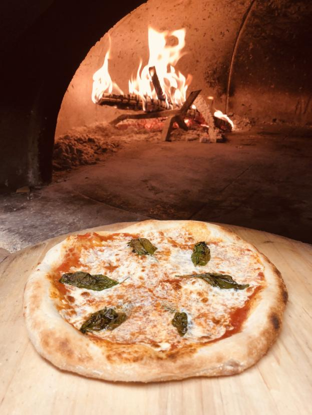 A margherita pizza from Forno Rosso Alaska (Courtesty of Forno Rosso Alaska.) A picture of a pizza next to a wood fire oven.