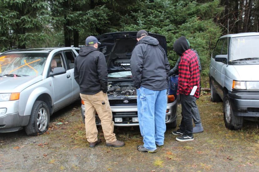 A group of prospective car buyers take a look under the hood of a Subaru at an auction at the city's impound lot in Lemon Creek, November 2018.