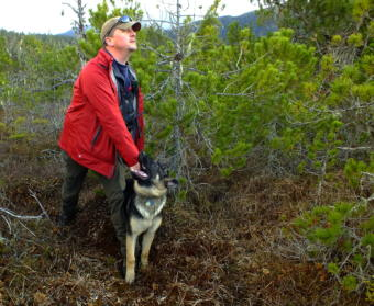 "SEADOGS' Liam Higgins holds on to Oskar, his 5 month old German Shepherd, while he looks to make sure that a volunteer is hidden before giving the command to ""Find him!"". (Photo by Matt Miller/KTOO)"