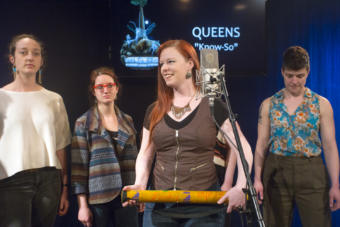 A woman holding a rain stick smiling around a microphone with other women in the background