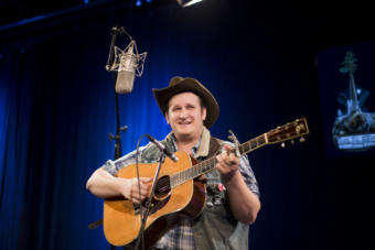 A man in a cowboy hat with a guitar sings into a microphone in the KTOO TV Studio in Juneau. Arkansas songwriter Willi Carlisle performs a Red Carpet Concert during the 2019 Alaska Folk Festival in the KTOO TV Studios. (Photo by Annie Bartholomew/KTOO)