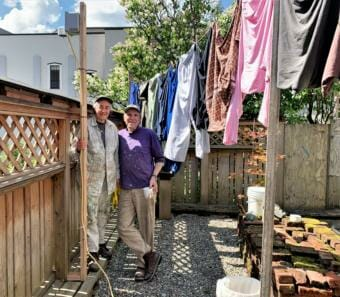 Martha and Jim Stey stand beneath the Purple Air air quality sensor installed by DEC in their backyard. They nicknamed the sensor Jon, after this late friend Jon Sandstedt. (Photo by Adelyn Baxter/KTOO)