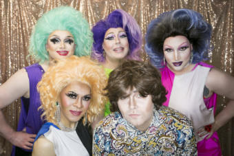 Drag performers stand in front of a gold background Juneau drag performers pose backstage at Centennial Hall for the 5th Annual GLITZ Drag Show and Juneau Pride Kickoff at Centennial Hall on Friday, June 14, 2019. Artists Lola Monèt, Shirley Wood, Miss Guise, Aura Borealis and Dear Evan Handsome took the stage for an opening number inspired by the 1969 Stonewall riots. (Photo by Annie Bartholomew/KTOO)