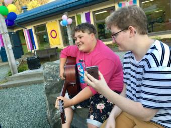 "Callum Marks (right) serves as a ""modern day page turner"" for Theo Houck, who played a set of queer love songs at Juneau's first youth Pride party on June 20, 2019. (Photo by Zoe Grueskin/KTOO)"