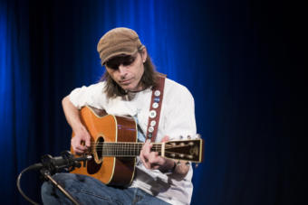 A man plays an acoustic guitar into a microphone on a blue background in a television studio. Guitarist Justin Smith performs a Red Carpet Concert at KTOO Public Media during the 2019 Alaska Folk Festival (Photo by Annie Bartholomew/KTOO)