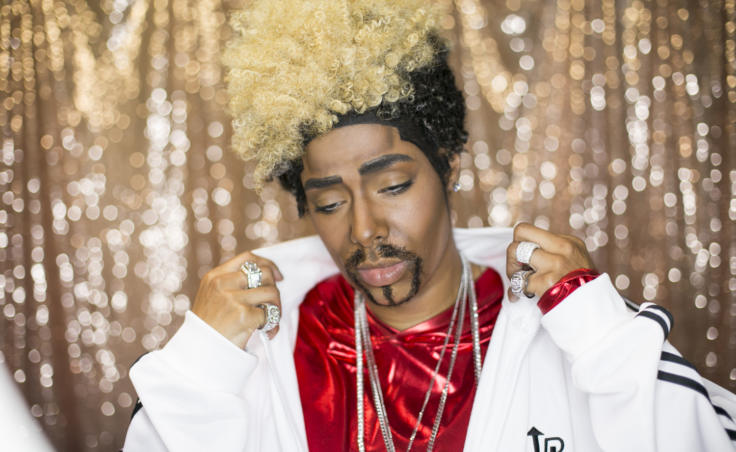 "A drag king in a white track jacket poses backstage with a blonde and black afro and goatee. Drag king and clothing designer Tahir McInnes who performs as the drag persona ""Tyquan"" as a member of the drag king ensemble ""The Seven Dudely Sins"" at Centennial Hall on Friday, June 14, 2019. The group danced to a medley of boy bands during their routine. (Photo by Annie Bartholomew/KTOO)"
