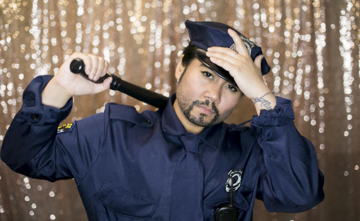 """A drag king with a baton poses backstage as a police officer. Juneau artist Christianne Carrillo who performs as the drag king """"Will Duja"""" poses backstage as police officers at Centennial Hall for the 5th Annual GLITZ Drag Show and Juneau Pride Kickoff at Centennial Hall on Friday, June 14, 2019. (Photo by Annie Bartholomew/KTOO)"""