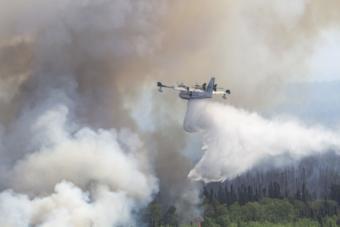 A plane assists in fighting a wildfire at Montana Creek near Talkeetna, Alaska, July 4, 2019.