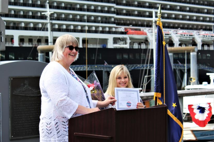 Mayor Beth Weldon presents Ashley DeRamus with a certificate honoring her for being the first person with Down Syndrome to sing the national anthem in all 50 states. (Photo by Adelyn Baxter/KTOO)
