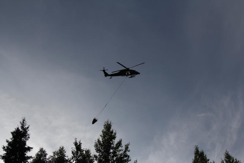 An Alaska National Guard Blackhawk helicopter circles after dropping a bucket of water on a wildfire in East Anchorage on Tuesday, July 2, 2019.