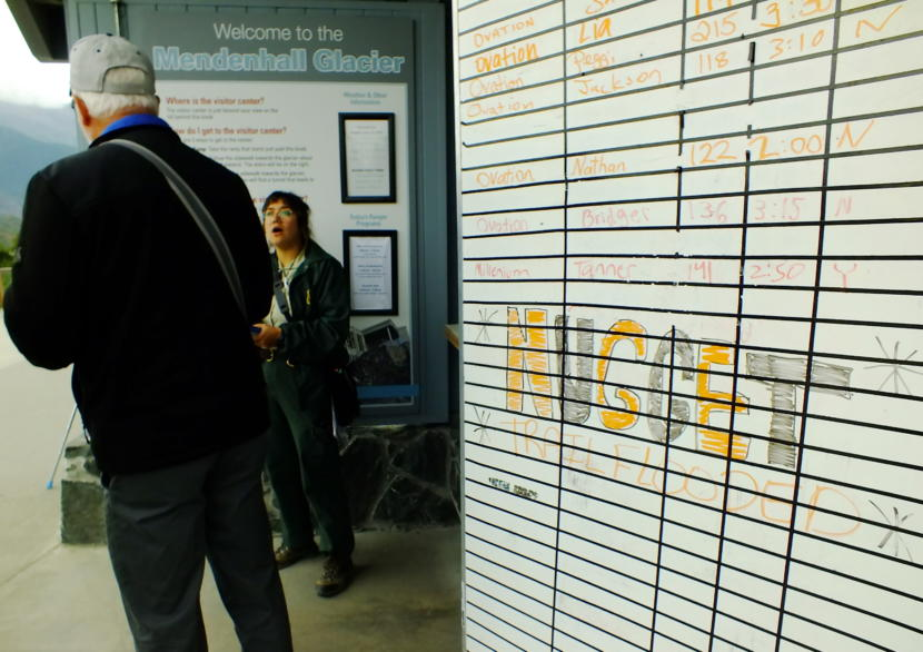 U.S. Forest Service interpreter Isabel Dzaik helps a tourist at the Mendenhall Glacier Visitor Center on July 14, 2019 as a nearby sign shows the closure of the Nugget Falls Trail because of a jökulhlaup or glacial dam release.