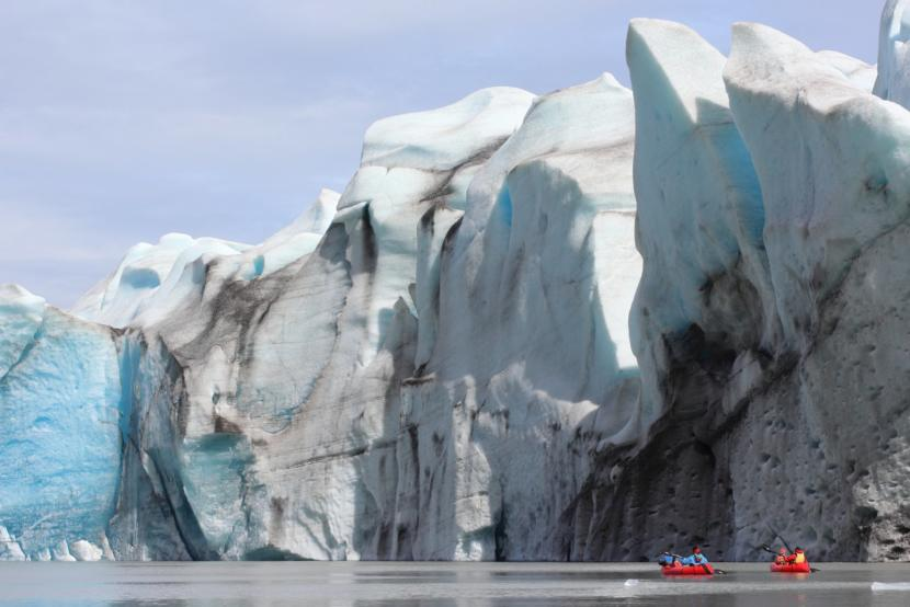 Two small boats row past the Grewingk Glacier.