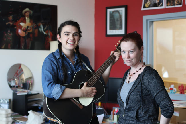 Two women with a guitar stand in front of a desk at KTOO Public Media. Juneau musicians Annie Bartholomew and Marian Call are performing at Friday's Souteast by Southwest: Music Showdown at the Gold Town Nickelodeon on August 2, 2019. Bartholomew is an Arts & Culture Producer at KTOO Public Media. (Photo by Stella Tallmon/KTOO Public Media)
