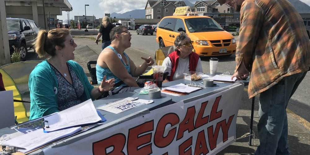 Recall Dunleavy volunteers Frankie Urquhart, left, Jessie Chapman and Pat Chapman gather signatures on Aug. 1 in downtown Ketchikan for a petition to remove Gov. Mike Dunleavy from office. (Photo by Elizabeth Gabriel/KRBD)