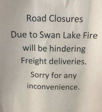 "A sign that says, ""Road Closures Due to Swan Lake Fire will be hindering freight deliveries. Sorry for any inconvenience."""