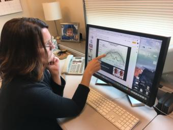 "Elizabeth Siddon, photographed in her office on Aug. 1, 2019, points to a figure charting sea ice extent in the Bering Sea, which shows a ""double whammy"" of back-to-back low sea ice winters in 2017-18 and 2018-19. (Photo by Zoe Grueskin/KTOO)"
