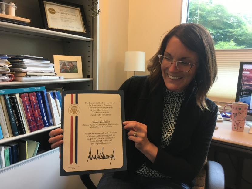 Elizabeth Siddon in her office on Aug. 1, 2019, displays her Presidential Early Career Award for Scientists and Engineers (Photo by Zoe Grueskin/KTOO)