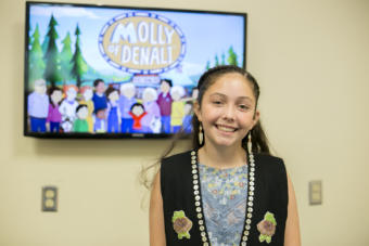 """A girl in a black vest stands in front of a tv screen. Tlingit and Muckleshoot actress Sovereign Bill poses at a voice-over workshop at KTOO Public Media before the Juneau premiere of the PBS KIDS show """"Molly of Denali"""" Saturday, August 10 at 9:30 a.m. at Elizabeth Peratrovich Hall."""