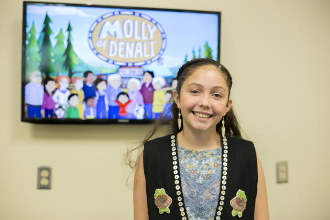 "A girl in a black vest stands in front of a tv screen. Tlingit and Muckleshoot actress Sovereign Bill poses at a voice-over workshop at KTOO Public Media before the Juneau premiere of the PBS KIDS show ""Molly of Denali"" Saturday, August 10 at 9:30 a.m. at Elizabeth Peratrovich Hall."
