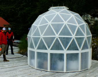 In this picture taken in early June 2019, Tom Lafollette, caretaker of the Annex Creek Hydroelectric Facility in Taku Inlet (obscured behind left side of greenhouse), explains to visitors how he built this scratch-built geodesic greenhouse for growing tomatoes, peppers, and other vegetables. The greenhouse is about 10 feet in diameter and is a slightly smaller version than a previous greenhouse he constructed from plans.