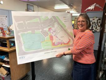 Juneau Arts and Humanities Council Executive Director Nancy DeCherney holds an aerial view of the design for the New JACC. (Photo by Adelyn Baxter/KTOO)