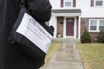 A man with a U.S. Census Bureau bag stands outside the front door of a suburban home.