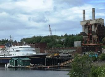 The Alaska Marine Highway System ferry Taku is in storage at Ketchikan's Ward Cove. The former Ketchikan Pulp Co. mill site, including ferry headquarters, is in the background. (Photo by Leila Kheiry/KRBD)
