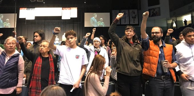 Protesters stand with their back to the stage during Gov. Mike Dunleavy's speech at the AFN Convention in Fairbanks on Thursday, Oct. 17, 2019.