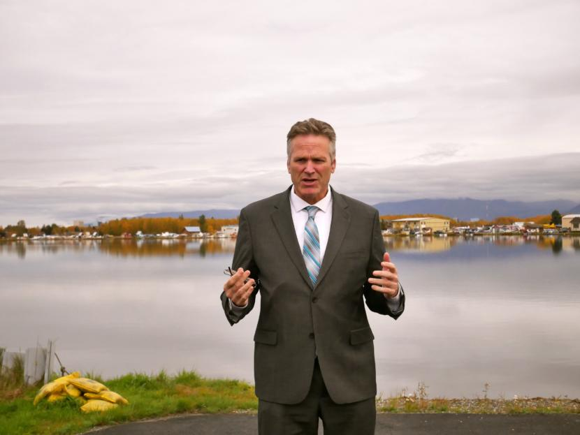 Gov. Mike Dunleavy addresses reporters on the bank of Lake Hood after touring cargo operations at Ted Stevens Anchorage International Airport.