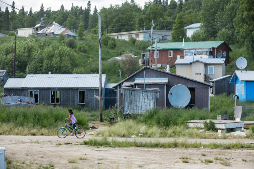 Syra Kozevnikoff, 9, rides her bicycle along a road on June 28, 2019 in Russian Mission. The tan building behind her is the village public safety office, which has three jail cells that are rarely used. (Photo by Loren Holmes/Anchorage Daily News)
