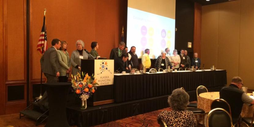 Mayors and representatives from 15 Alaska communities sign an agreement establishing a statewide commission to coordinate online sales tax collection. The ceremony took place at the annual Alaska Municipal League conference in Anchorage on Thursday, Nov. 21, 2019. (Photo courtesy of Michelle Hale)