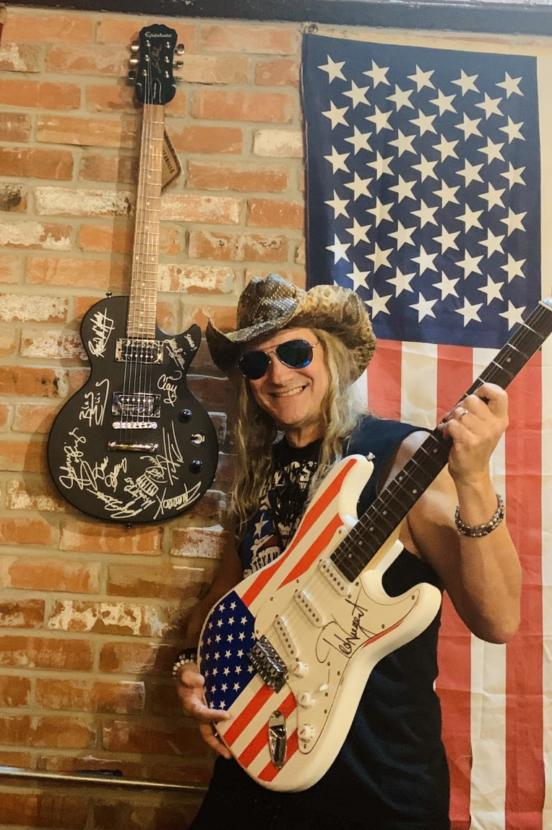 Johnny Solinger poses with a guitar signed by Ted Nugent at the Pacific Yard House in Conroe, Texas. The guitar on the wall is one of eight he owns that he and other rock stars signed that he intends to auction off for charity, including one to help Alaska veterans.