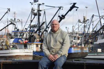 Cod fisherman Frank Miles sits on the deck of the Sumner Strait, docked in Kodiak's St. Paul Harbor. (Photo by Kavitha George/Alaska's Energy Desk)