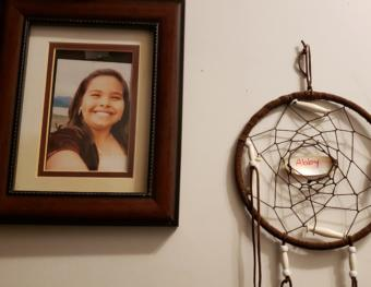 """A photo of Abby Kelley and a dream catcher hang on a wall in her family's home in Juneau on Dec. 2, 2019. Her parents say that she """"had dimples for days."""""""