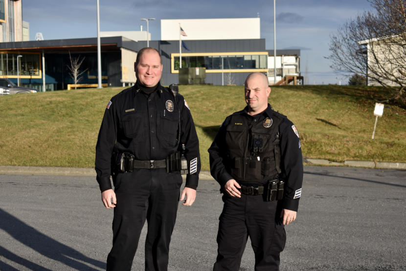 Two police officers pose outside for a photo.