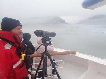 National Park Service scientist Scott Gende spots for whales and logs their behavior from the deck of the Noordam in Glacier Bay, Alaska. The cruise line has been providing space for federal whale observers in the national park since 2006. (Photo by Jacob Resneck/Coast Alaska)