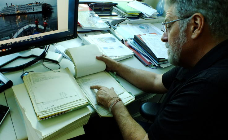 Paul Webb, who served aboard the U.S. Coast Guard buoy tender Woodrush during the Prisendam fire, goes through an archived file of documents preserved from the original search and rescue operation. On the computer screen in front of him is a picture of another cruise ship that encountered trouble in Southeast Alaska, the sternwheeler Empress of the North, which grounded on a rock near Juneau in 2007. (Photo by Matt Miller/KTOO)