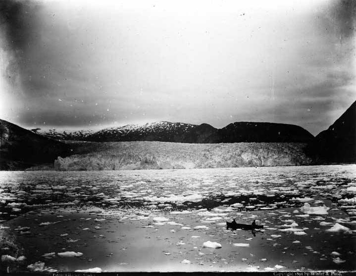 Two figures paddle a canoe amidst floating ice with Taku Glacier in background, circa 1895 (Alaska State Library - Historical Collections ASL-P87-1952)