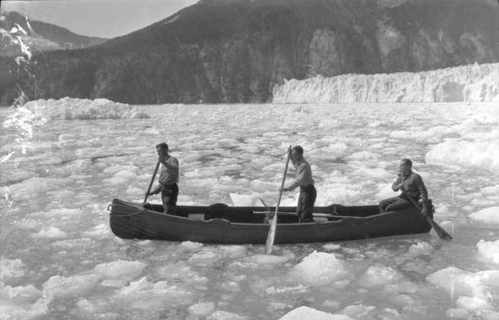 Three men paddling canoe in ice before Taku Glacier. Left to right: Ben Wood, W. O. Field and Roscoe Bonsal. (P87-1981 Alaska State Library - Winter and Pond Photo Collection)