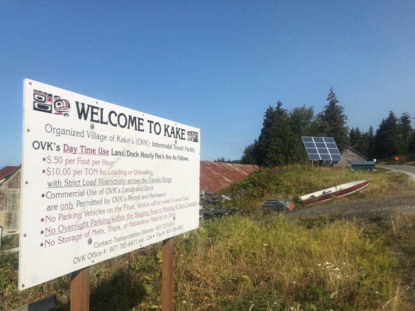 "A sign that says ""Welcome to Kake"" in the foreground, with a solar panel in the background."