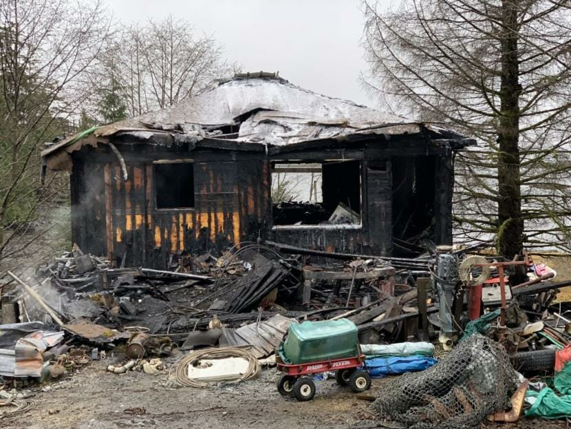 A small house smolders after burning in a fire.
