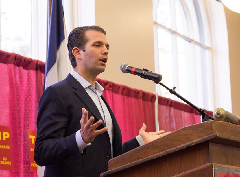 Donald Trump Jr. speaks into a microphone at a podium.