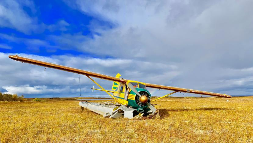 A small single-propeller floatplane sits in a yellow field, its landing gear crushed underneath.