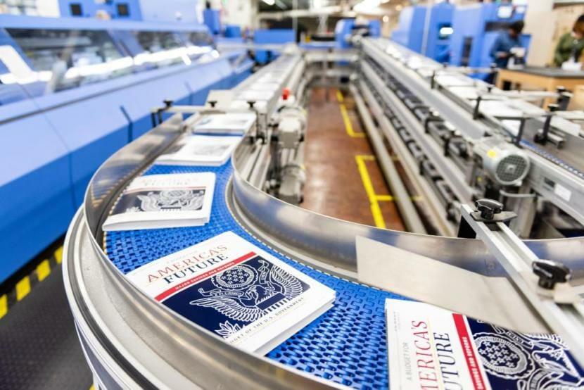 Copies of the president's fiscal year 2021 budget move down a conveyor belt.