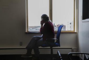 Anchorage School District nurse Elida Spiro sits in an empty room at the Anchorage Health Department Tuesday, March 31, 2020 as she makes contact with a person that has been quarantined due to possible exposure to Covid-19. (Photo courtesy Robert DeBerry/Anchorage School District)
