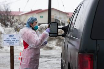 Registered Nurse Avelina Chung runs through protocol with a YKHC employee at the COVID-19 drive-thru test site on March 25, 2020 in Bethel, Alaska. Credit Katie Basile / KYUK