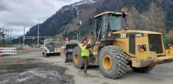 SECON worker Dartanan Campos hops into the cab of construction equipment near the intersection of Egan Drive and 10 Street in Juneau on May 6, 2020.