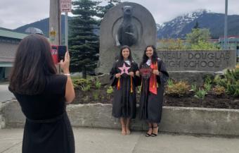 Maya Araujo, left and Jade Araujo pose for graduation photos outside Juneau-Douglas High School: Yadaa.at Kale on May 18, 2020.